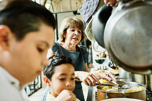 Grandsons helping grandmother prepare food in kitchen for family dinner - gettyimageskorea