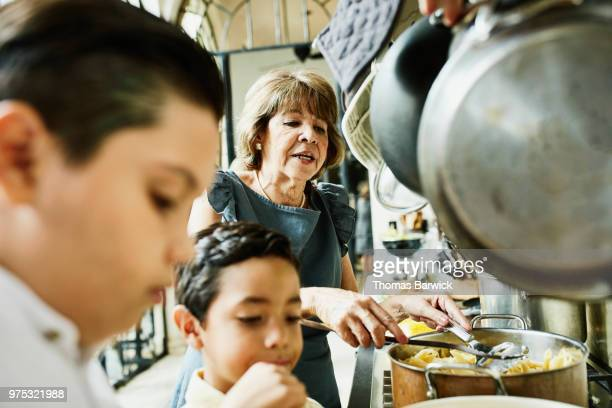 Grandsons helping grandmother prepare food in kitchen for family dinner