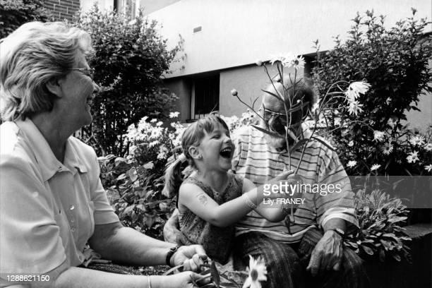Grands-Parents retraités et leur petite fille s'amusant et cueillant des fleurs dans leur jardin, Vitry-sur-Seine, Val-de-Marne France.