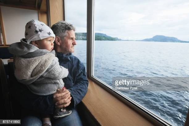granfather with grandchild looking at ocean from ferry - ferry photos et images de collection