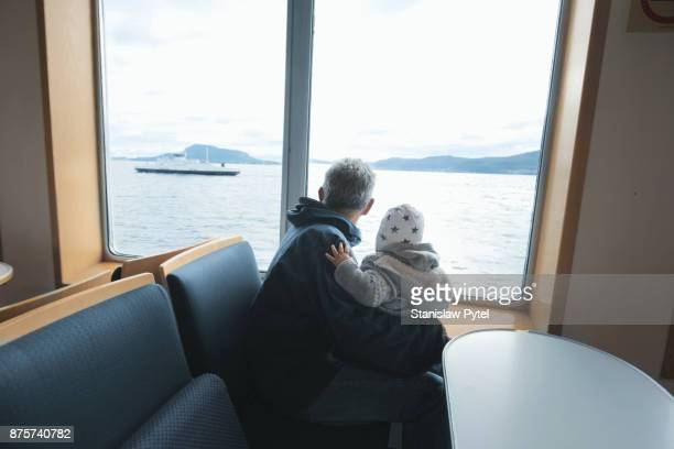 Granfather with grandchild on ferry looking at ocean and ship