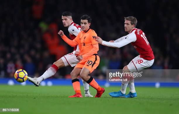 Granit Xhaka and Nacho Monreal of Arsenal battle with Philippe Coutinho of Liverpool during the Premier League match between Arsenal and Liverpool at...