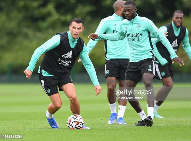 Granit Xhaka and Nicolas Pepe of Arsenal during a training session at London Colney on July 30, 2021 in St Albans, England.