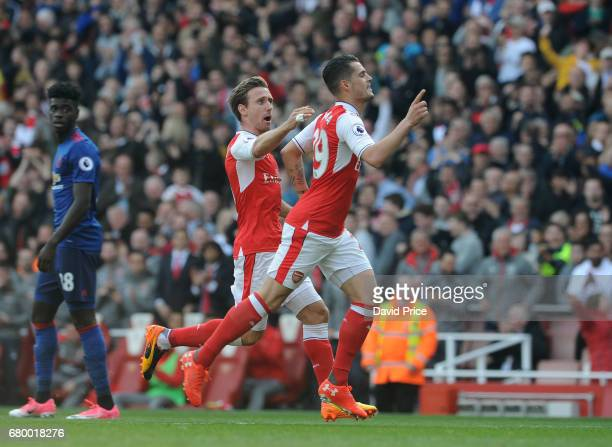 Granit Xhaka celebrates scoring Arsenal's 1st goal with Nacho Monreal during the Premier League match between Arsenal and Manchester United at...