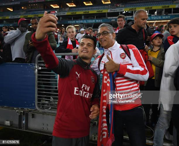 Granit Xhaka has a selfie with an Arsenal fan after a training session at the ANZ Stadium on July 14 2017 in Sydney New South Wales