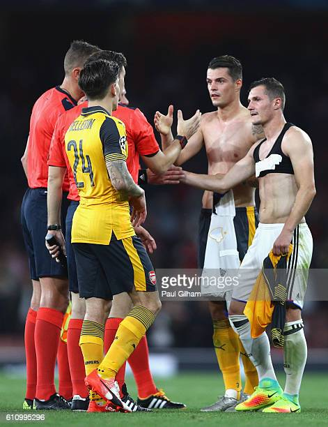 Granit Xhaka of Arsenal and Taulant Xhaka of Basel shake hands with the match officials at the end of the UEFA Champions League group A match between...