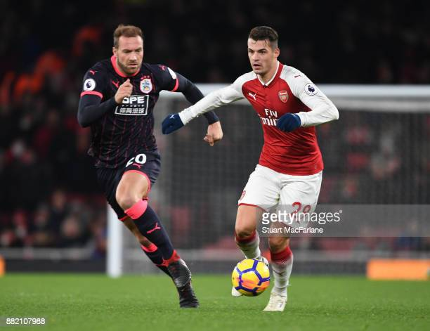 Granit Xhaka of Arsenal breaks past Laurent Depoitre of Huddersfield during the Premier League match between Arsenal and Huddersfield Town at...