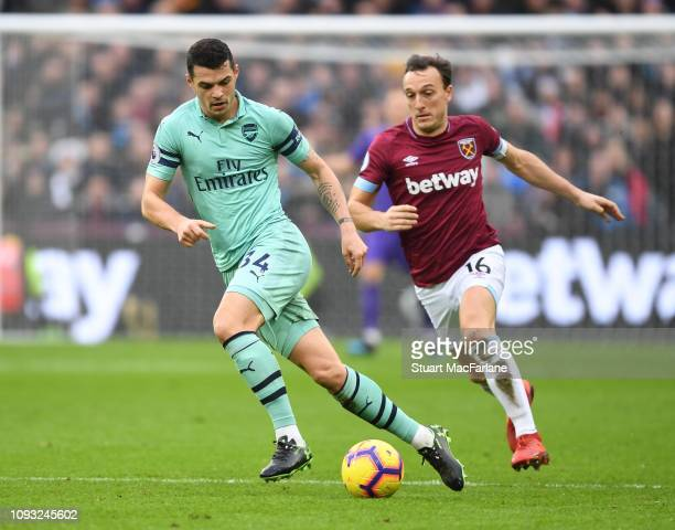 Granit Xhaka of Arsenal breaks past Mark Noble of West Ham during the Premier League match between West Ham United and Arsenal FC at London Stadium...