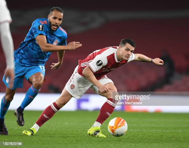 Granit Xhaka of Arsenal breaks past Youssef El Arabi of Olympiacos during the UEFA Europa League Round of 16 Second Leg match between Arsenal and...