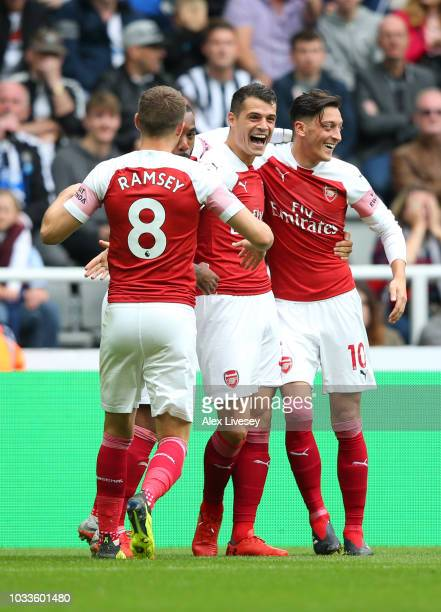 Granit Xhaka of Arsenal celebrates with teammates after scoring his team's first goal during the Premier League match between Newcastle United and...