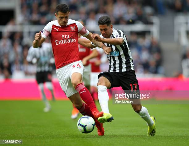Granit Xhaka of Arsenal challenges for the ball with Ayoze Perez of Newcastle United during the Premier League match between Newcastle United and...
