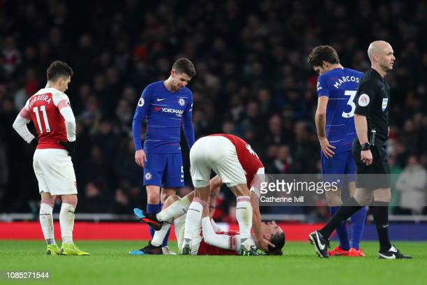 Granit Xhaka of Arsenal consults teammmate Hector Bellerin of Arsenal as he goes down injured during the Premier League match between Arsenal FC and...