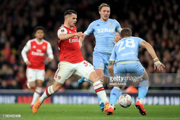 Granit Xhaka of Arsenal in action with Luke Ayling and Gaetano Berardi of Leeds United during the FA Cup Third Round match between Arsenal and Leeds...
