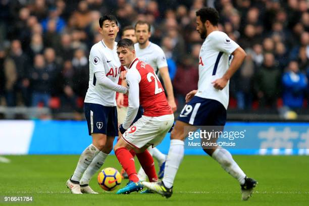 Granit Xhaka of Arsenal in action with Son Heungmin and Mousa Dembele of Tottenham Hotspur during the Premier League match between Tottenham Hotspur...