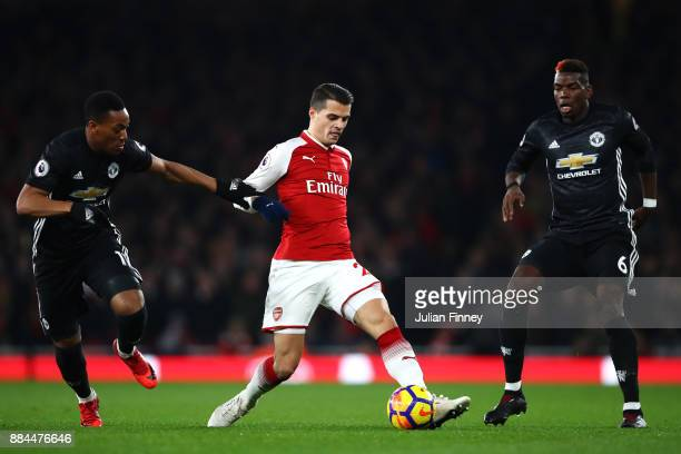 Granit Xhaka of Arsenal is challenged by Anthony Martial of Manchester United and Paul Pogba of Manchester United during the Premier League match...