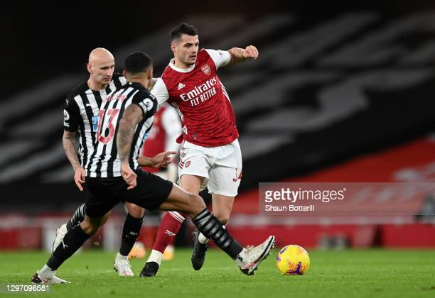 Granit Xhaka of Arsenal is challenged by Callum Wilson and Jonjo Shelvey of Newcastle United during the Premier League match between Arsenal and...