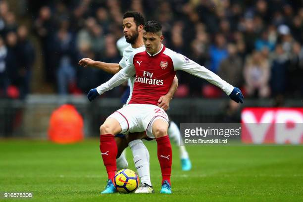 Granit Xhaka of Arsenal is challenged by Mousa Dembele of Tottenham Hotspur during the Premier League match between Tottenham Hotspur and Arsenal at...