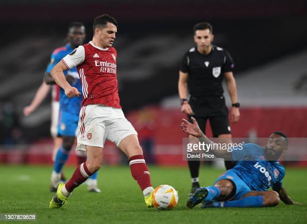 Granit Xhaka of Arsenal is challenged by Yann M'Vila of Olympiacos during the UEFA Europa League Round of 16 Second Leg match between Arsenal and...