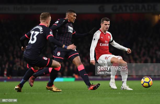 Granit Xhaka of Arsenal is closed down by Florent Hadergjonaj and Colin Quaner of Huddersfield during the Premier League match between Arsenal and...