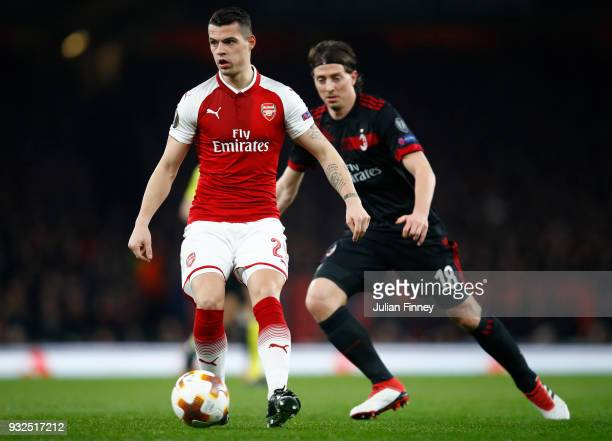 Granit Xhaka of Arsenal keeps the ball from Riccardo Montolivo of AC Milan during the UEFA Europa League Round of 16 Second Leg match between Arsenal...