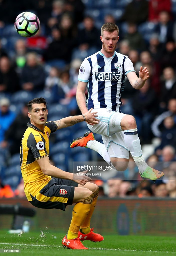 Granit Xhaka of Arsenal (L) looks on as Chris Brunt of West Bromwich Albion (R) wins a header during the Premier League match between West Bromwich Albion and Arsenal at The Hawthorns on March 18, 2017 in West Bromwich, England.
