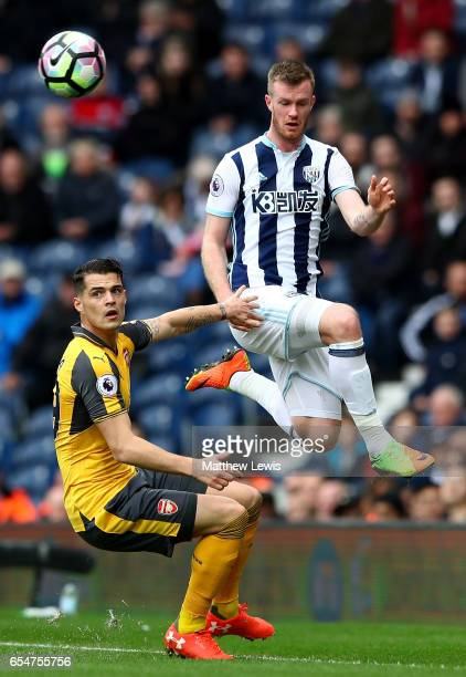 Granit Xhaka of Arsenal looks on as Chris Brunt of West Bromwich Albion wins a header during the Premier League match between West Bromwich Albion...