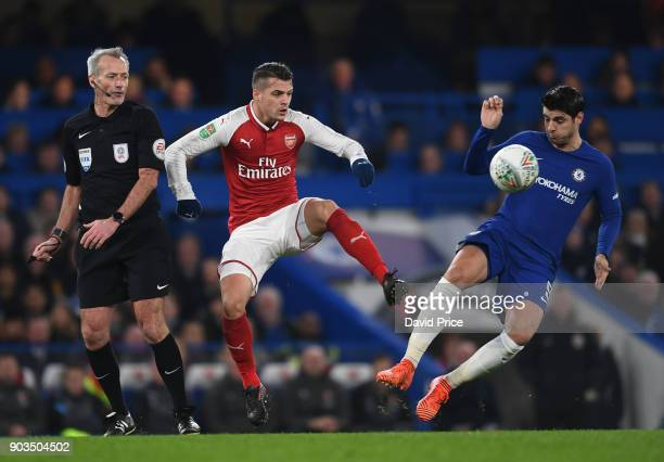 Granit Xhaka of Arsenal passes the ball under pressure from Alvaro Morata of Chelsea and Referee Martin Atkinson during the Carabao Cup Semie Final...