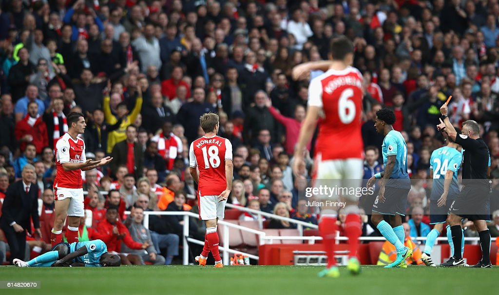 Granit Xhaka of Arsenal (L) reacts to being shown a red card by referee Jonanthan Moss during the Premier League match between Arsenal and Swansea City at Emirates Stadium on October 15, 2016 in London, England.