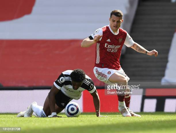 Granit Xhaka of Arsenal takes on Ola Aina of Fulham during the Premier League match between Arsenal and Fulham at Emirates Stadium on April 18, 2021...