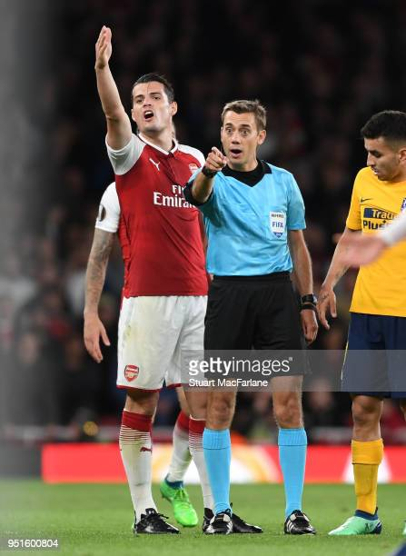 Granit Xhaka of Arsenal with referee Clement Turpin during the UEFA Europa League Semi Final leg one match between Arsenal FC and Atletico Madrid at...