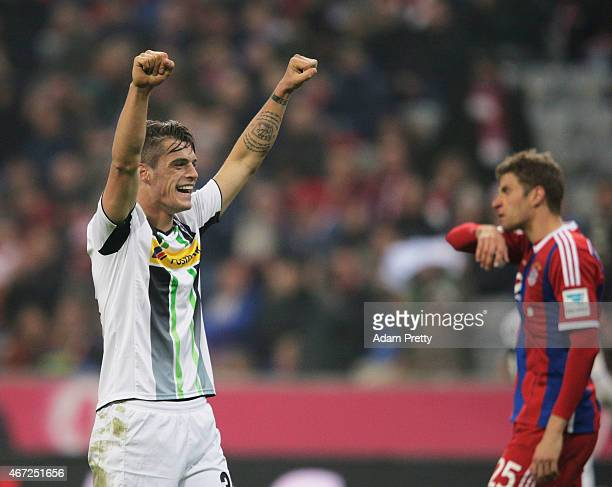 Granit Xhaka of Borussia Moenchengladbach celebrates victory in front of a dejected Thomas Mueller of FC Bayern Muenchen during the Bundesliga match...