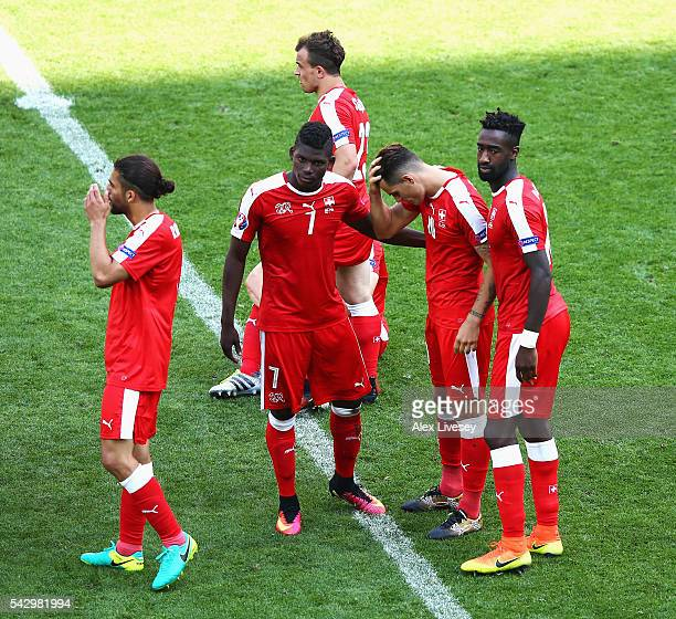 Granit Xhaka of Switzerland is consoled by his team mates after their defeat through the penalty shootout after the UEFA EURO 2016 round of 16 match...