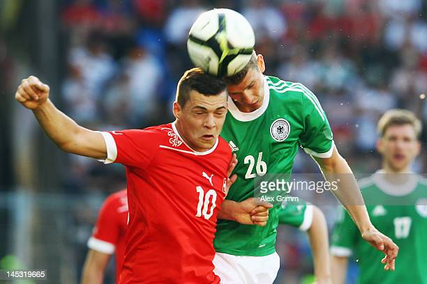 Granit Xhaka of Switzerland jumps for a header with Lars Bender of Germany during the international friendly match between Switzerland and Germany at...