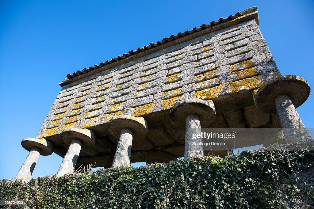 Granite granary on stone pillars : Stock Photo