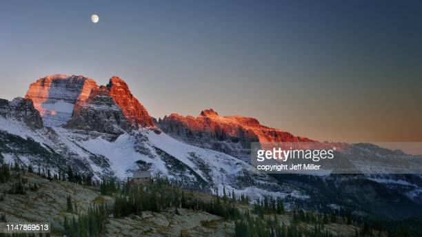 granite park chalet beneath snow capped mountains and rising moon at sunset, glacier national park, montana, usa. - montana fotografías e imágenes de stock