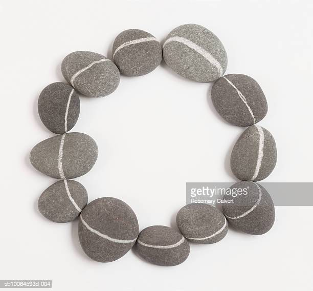 Granite pebbles arranged in form of circle on white background,, close-up