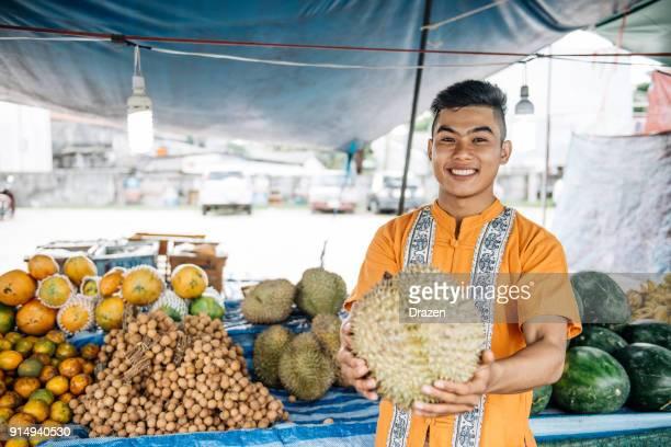 Granjero exitoso está vendiendo durian en el mercado en Tailandia