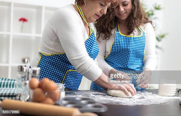 Granny and granddaughter preparing bread