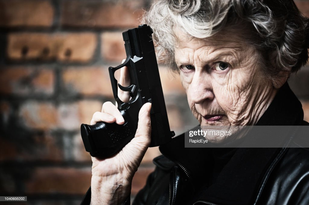 Granny get your gun! Fierce old woman holds pistol : Stock Photo