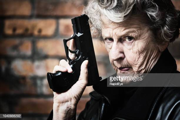 granny get your gun! fierce old woman holds pistol - criminal stock pictures, royalty-free photos & images