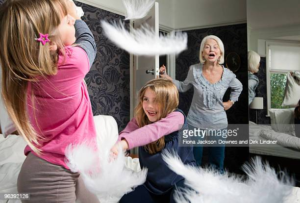 A granny shouts at girls pillow fighting