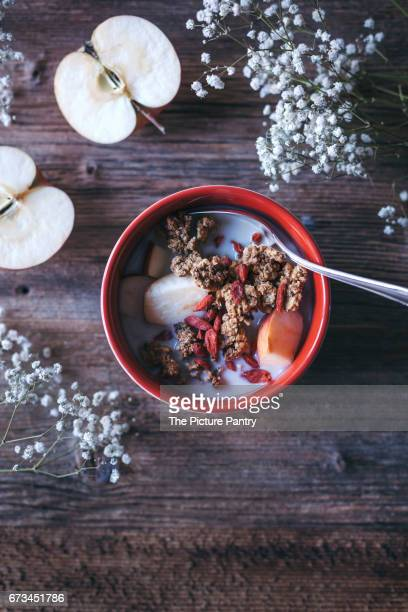 Granola with apples, goji berries and oat milk served in a bowl