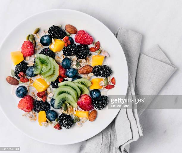 granola with milk and a variety of fresh and dried fruits - nut food stock photos and pictures
