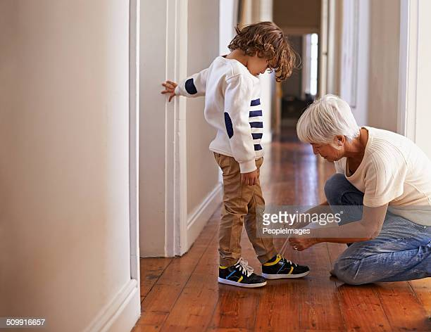 gran's helping him out on this one - shoelace stock pictures, royalty-free photos & images