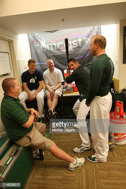 Grant Balfour shows off his batting stance as Andrew Bailey Michael Wuertz and the clubhouse staff look on before the game against the Minnesota...
