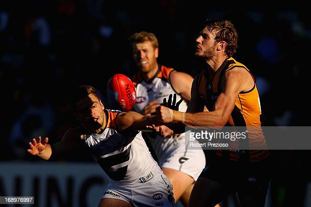 Grant Birchall of the Hawks handballs under pressure during the round eight AFL match between the Hawthorn Hawks and the Greater Western Sydney...