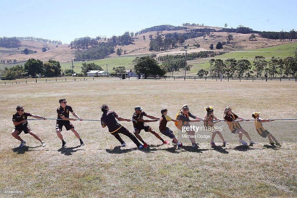 Grant Birchall, Taylor Duryea, Zac Webster and Dayle Garlett join kids in a Tug Of War contest at the Bream Creek Oval during the Hawthorn Hawks AFL Tasmania Community Camp on February 23, 2014 in Bream Creek, Australia.