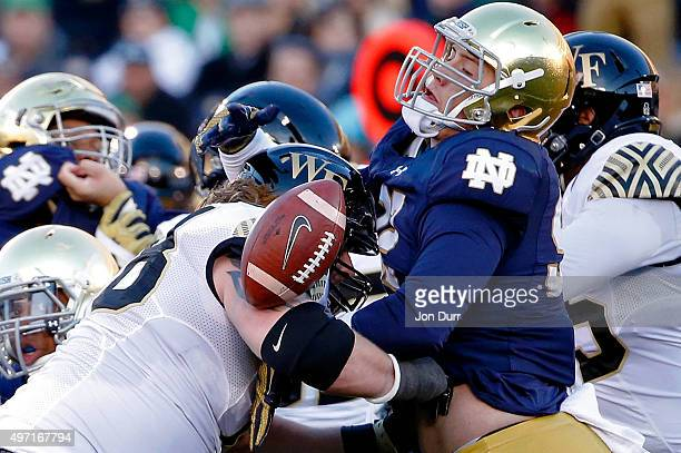 Grant Blankenship of the Notre Dame Fighting Irish is unable to make a play on a fumble while being defended by Tyler Hayworth of the Wake Forest...