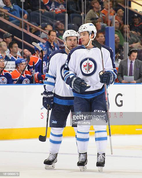 Grant Clitsome and Zach Redmond of the Winnipeg Jets confer between play against the Edmonton Oilers during a preseason NHL game at Rexall Place on...