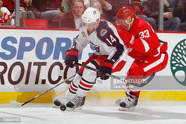 Grant Clitsome of the Columbus Blue Jackets battles for the puck with Kris Draper of the Detroit Red Wings during an NHL game at Joe Louis Arena on...
